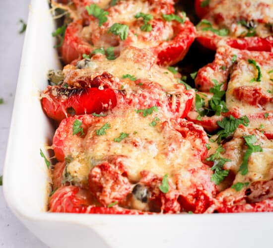 Bright red turkey stuffed pepper halves in a white baking dish with handles