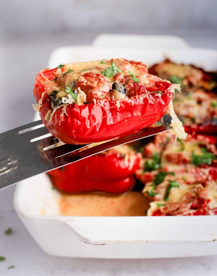 A spatula holding a single Southwestern turkey stuffed pepper half over a pan containing the remaining stuffed peppers