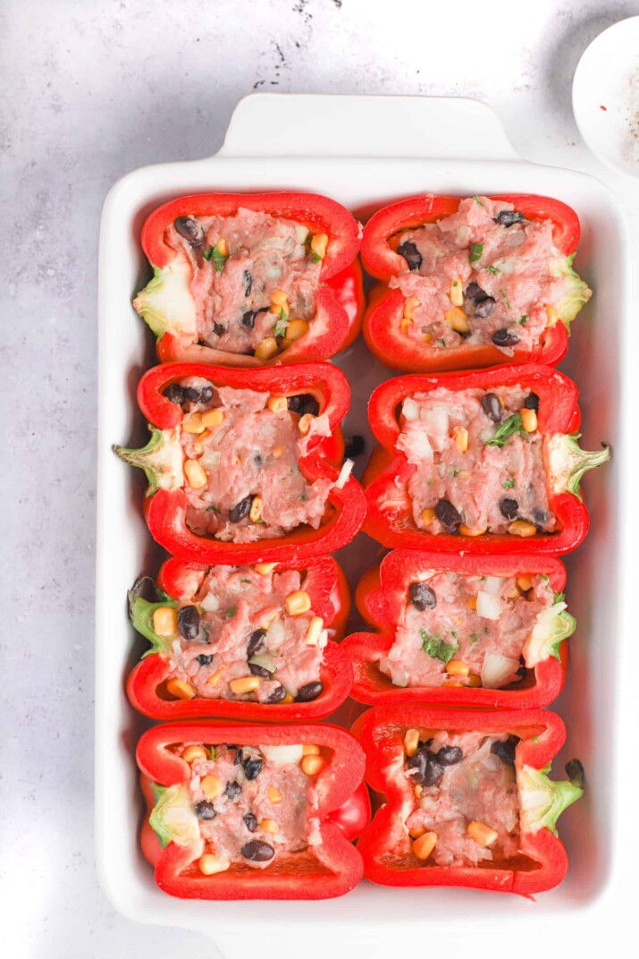 Eight filled red pepper halves in a white baking dish on a marble countertop