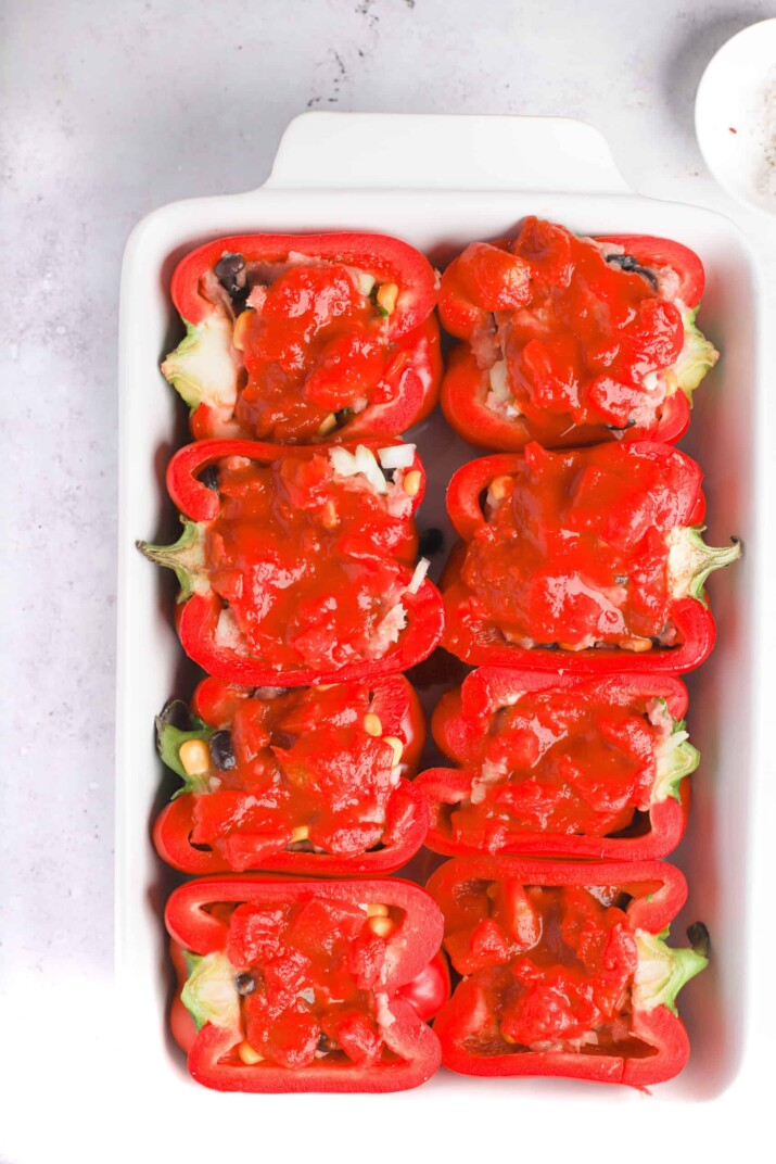 Eight stuffed pepper halves topped with fire roasted tomatoes