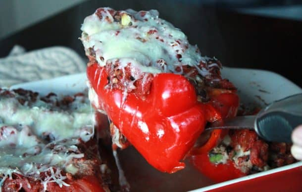 A Turkey Stuffed Red Pepper Being Lifted from a Red Pan