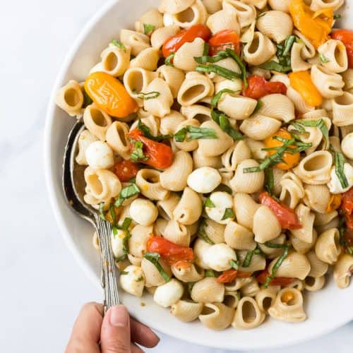 roasted tomato caprese pasta salad in a bowl with a hand holding a spoon