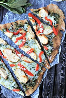 Five Slices of Grilled Chicken Pesto Pizza on a Wooden Surface