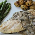 A Plate of Chicken with Creamy Mushroom Sauce and Veggies on the Side