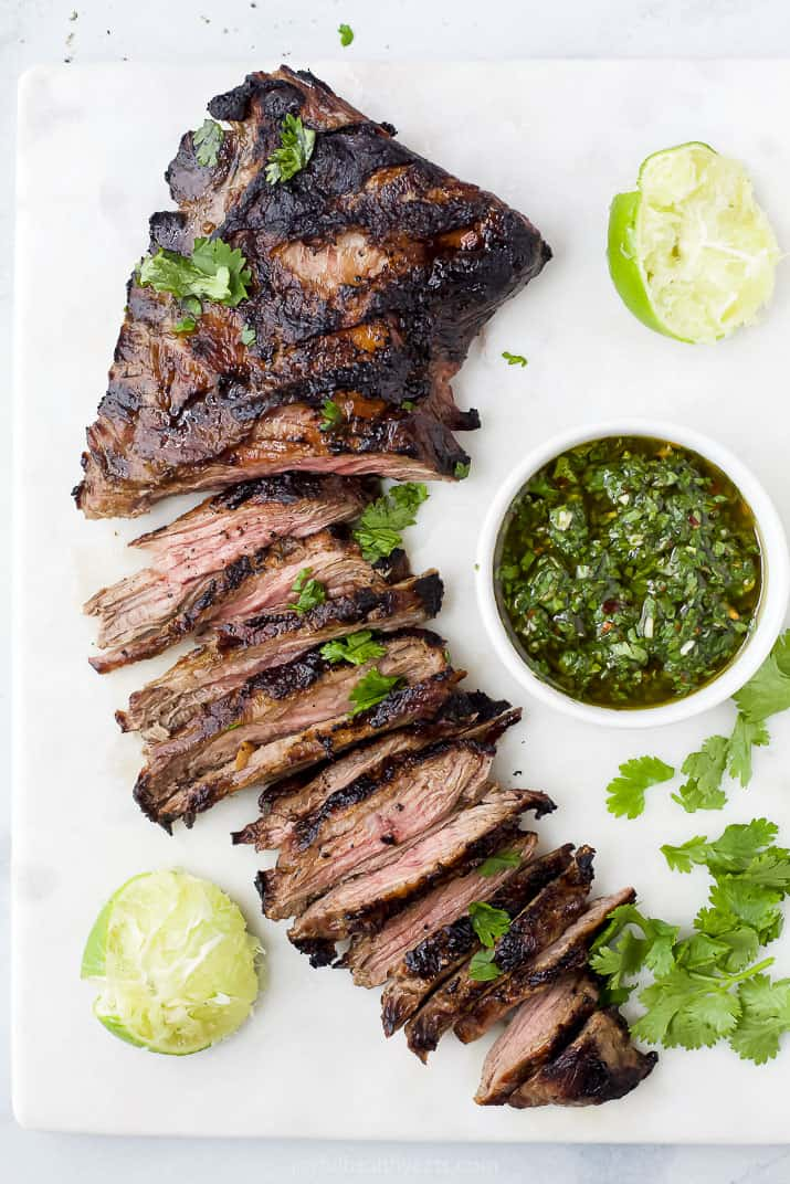 Grilled skirt steak on a cutting board with a bowl of chimichurri and lime
