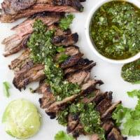 Skirt steak that's been partially sliced topped with chimichurri sauce