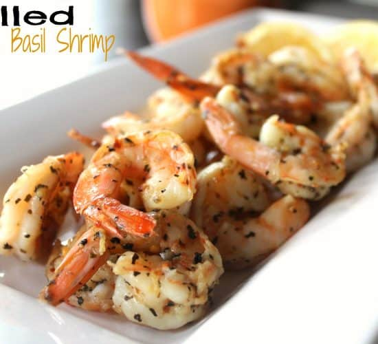 Grilled Garlic Basil Shrimp on a White Serving Plate with Lemon Slices