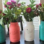 Four Brightly Painted Mason Jars Filled with Flower Bouquets