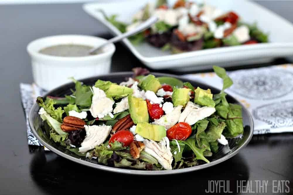 A bowl of salad greens topped with chicken, avocado, pecans, and tomatoes