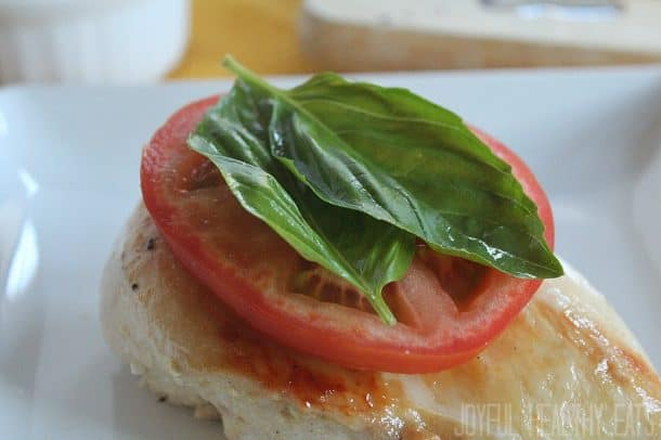 Chicken breast with sliced tomato and fresh basil