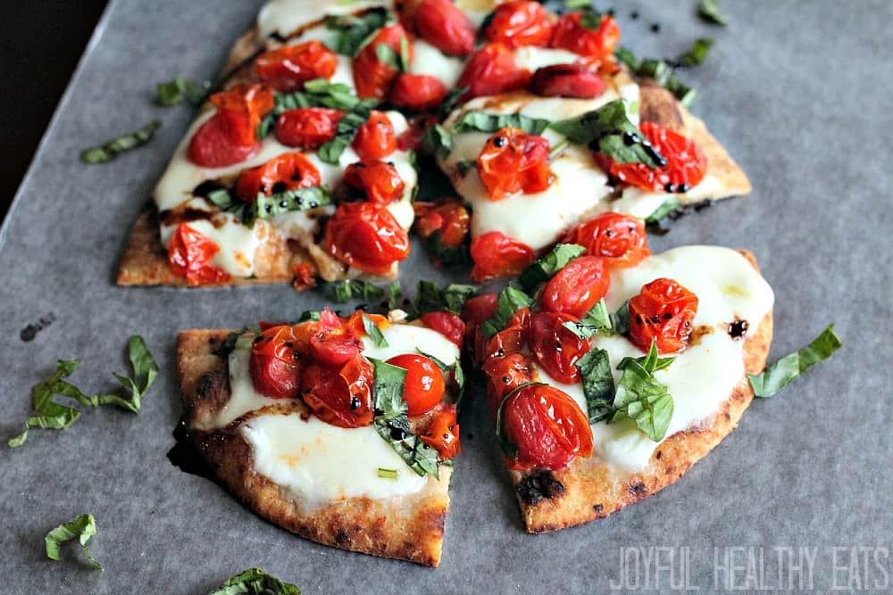 Caprese flatbread on parchment paper cut into 4 pieces