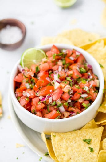 close up of easy homemade pico de gallo recipe in a bowl with chips around it