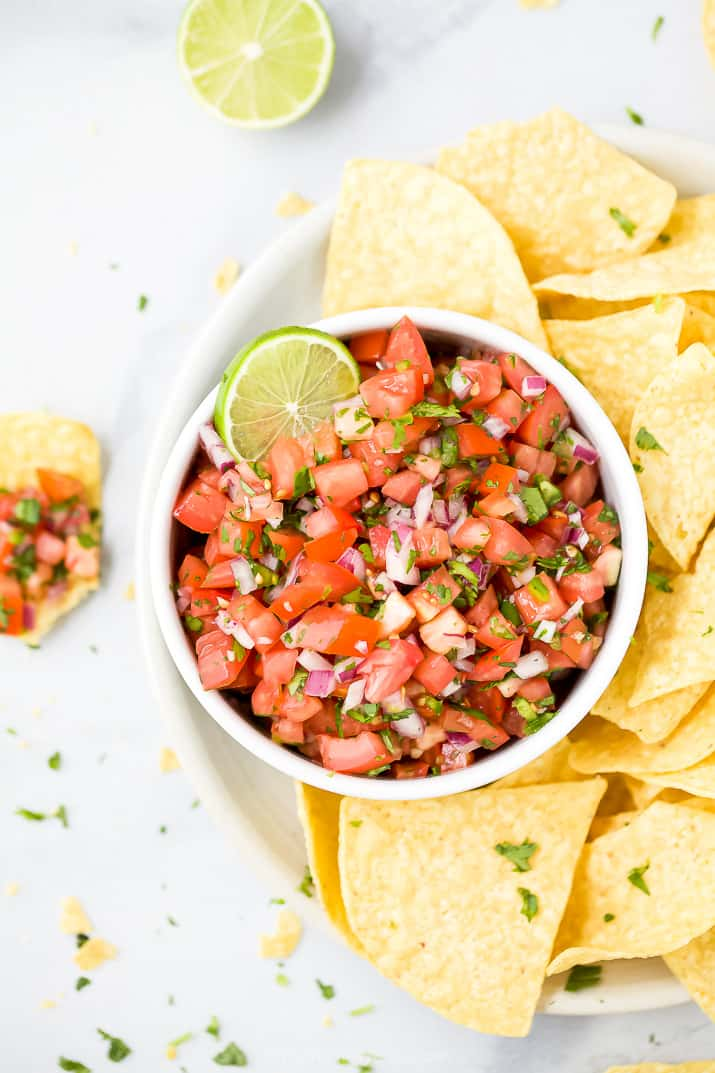fresh pico de gallo in a bowl served with chips