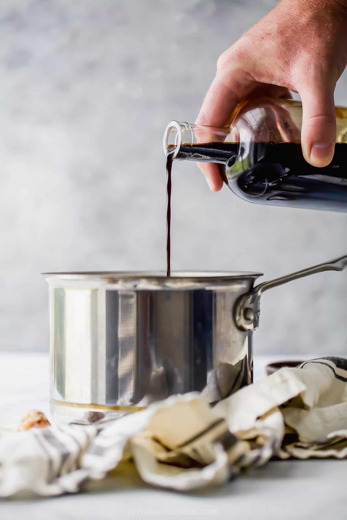 pouring balsamic vinegar into a pot