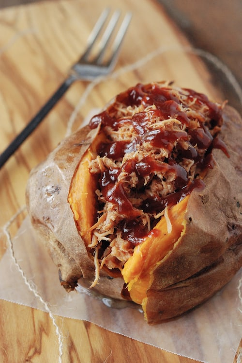 Top view of a roasted sweet potato topped with pulled pork