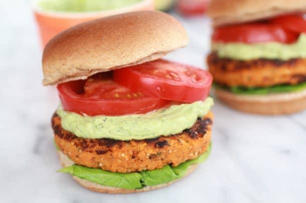 A sweet potato burger on a bun with avocado, tomato and avocado ranch sauce