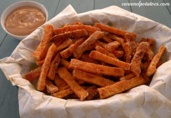 Sweet potato fries in a paper-lined basket with dipping sauce
