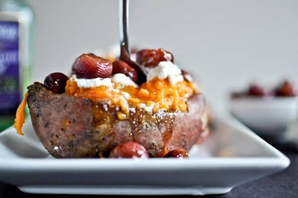 Roasted sweet potato topped with grapes and goat cheese on a plate