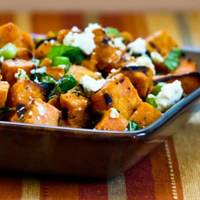 A square bowl of sweet potato salad with diced sweet potatoes, fresh herbs and crumbled cheese
