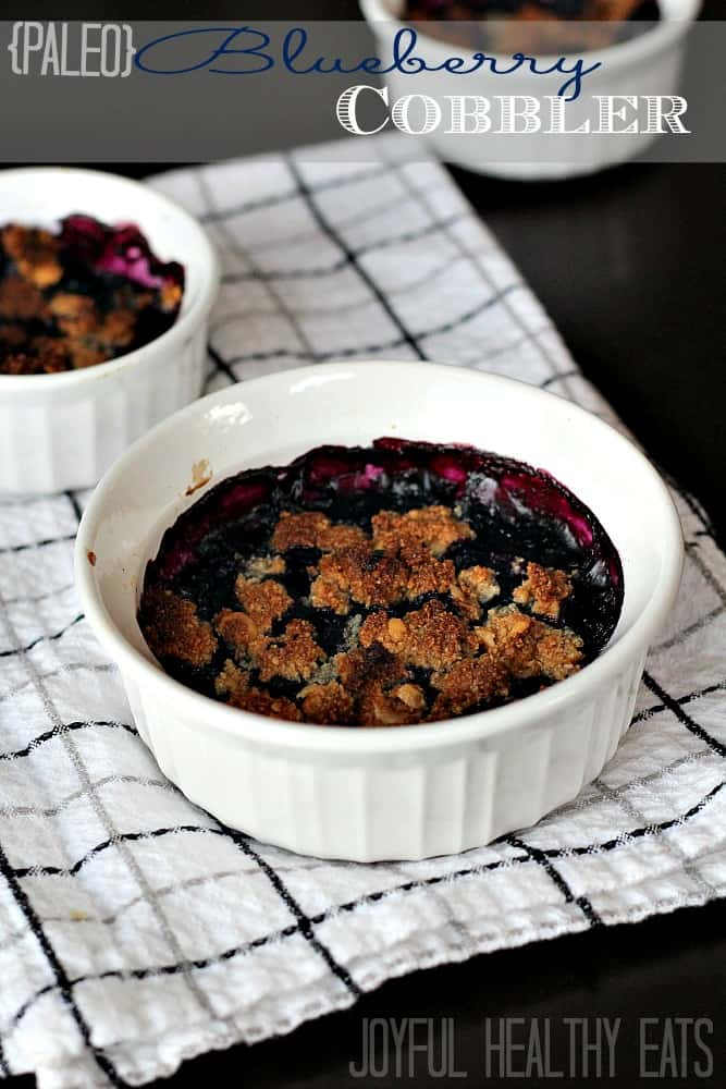 Two ramekins of Paleo Blueberry Cobbler with recipe title text