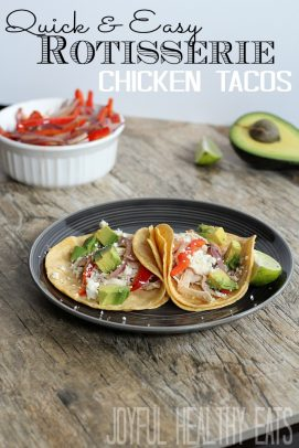 Shredded Chicken Tacos on a black plate and surrounded by fresh ingredients