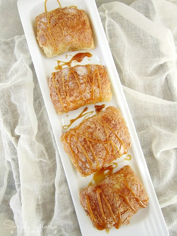 Four caramel pumpkin empanadas made with puff pastry on a white rectangular plate