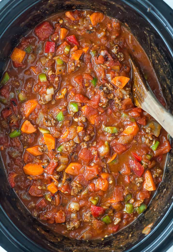 three bean chili in a crock pot with a wooden spoon