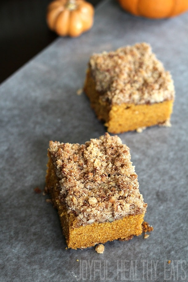 Two pieces of pumpkin spice coffee cake on a countertop with a small pumpkin in the background