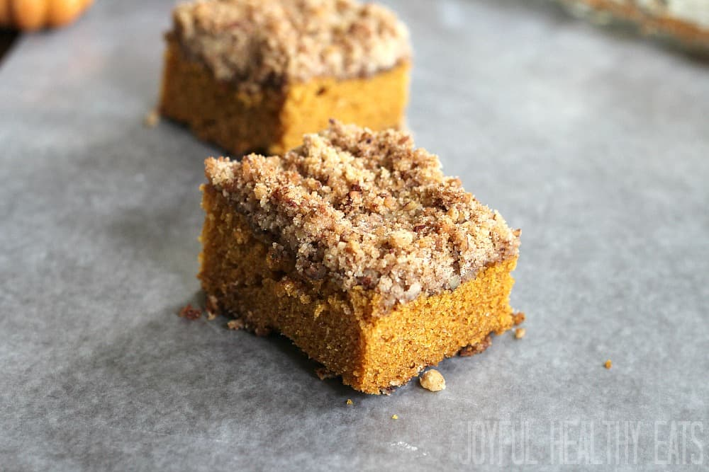 Two slices of pumpkin coffee cake with pecan streusel on a gray surface