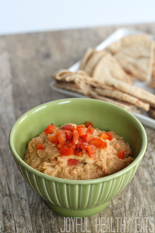 A green bowl of red pepper hummus