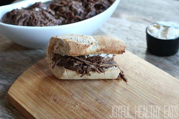 A shredded beef sandwich on a toasted bun with horseradish aioli on a wooden cutting board