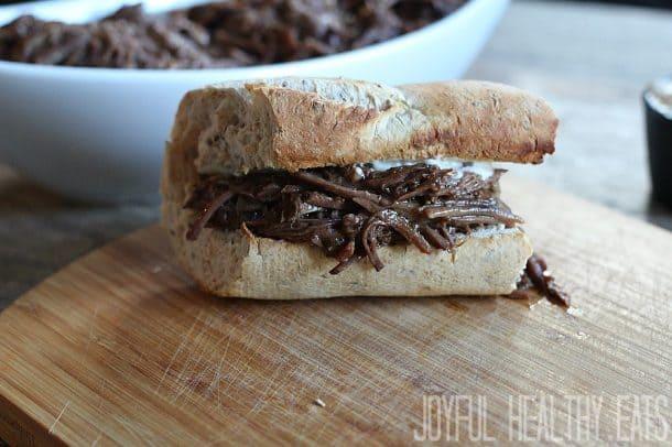 A toasted sandwich bun with shredded beef and horseradish aioli