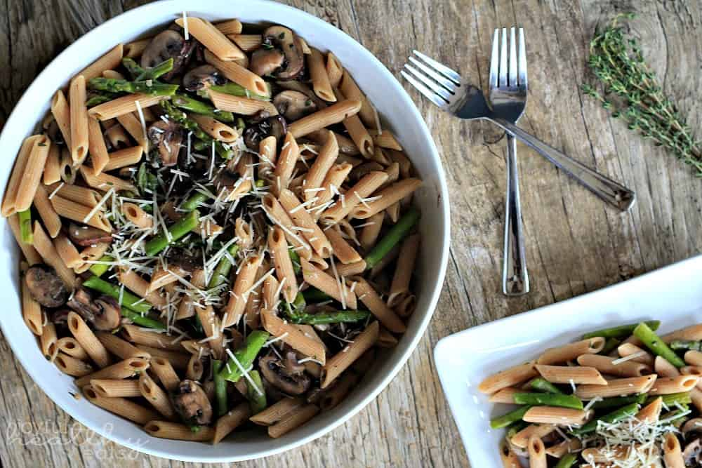 Asparagus & Mushroom Pasta topped with shredded cheese in a serving bowl