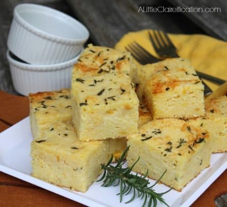 Squares of cornbread on a plate topped with rosemary and parmesan