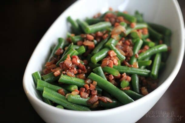 A bowl of green beans topped with pancetta and red onion