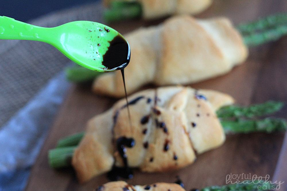 An Asparagus Rollup Being Drizzled with Balsamic Reduction