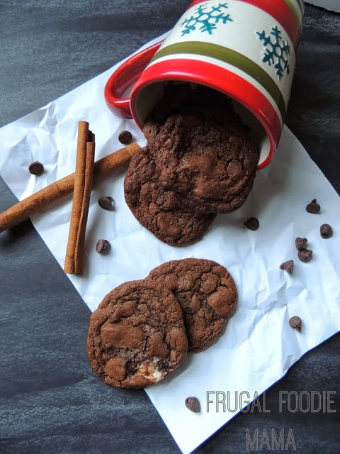 A tipped-over mug with cinnamon sticks and Mexican Hot Chocolate Cookies spilling out