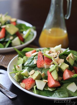 Strawberries and avocados on a fresh Spinach Salad with Honey Mustard Vinaigrette in a bottle behind it