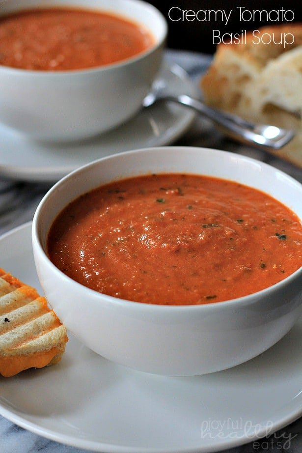 A bowl of Creamy Tomato Basil Soup on a plate with grilled cheese