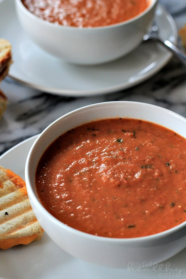 Top view of a bowl of Creamy Tomato Basil Soup with grilled cheese on a plate