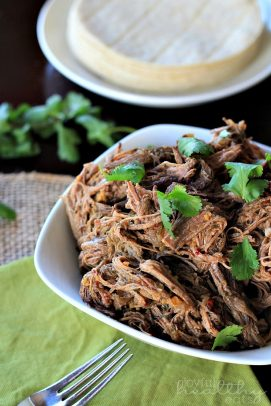 A bowl of shredded Beef Barbacoa with fresh herbs