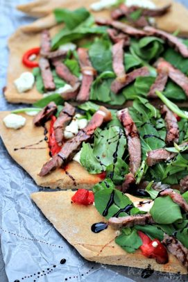 Homemade Pizza with Steak, Arugula, and Balsamic Reduction on tin foil
