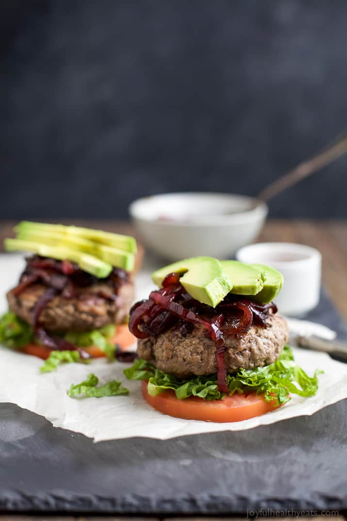 Who says burgers can't be healthy!? Paleo Burgers served on a slice of tomato topped with Caramelized Balsamic Onions that will make you swoon and of course Avocado! A quick 30 minute meal you're family will want on repeat! | joyfulhealthyeats.com #glutenfree
