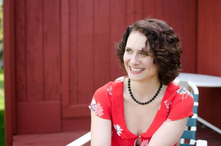 An adult woman with dark curly hair in a red floral top sitting in a chair outdoors in front of a red building