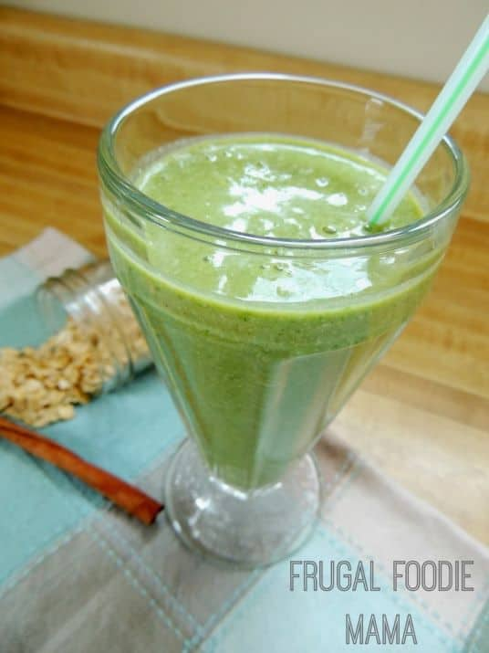A tall glass of green smoothie with a straw