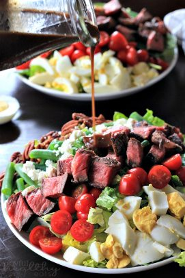 Steak Cobb salad being drizzled with balsamic vinegarette