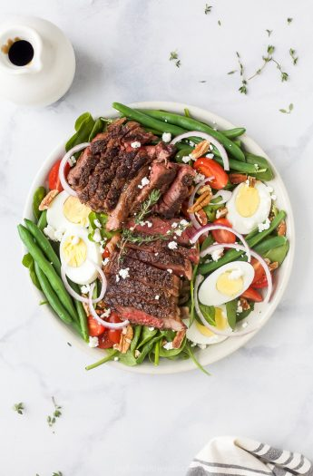 overhead photo of the ultimate ribeye steak salad with hardboiled eggs, tomatoes, onions