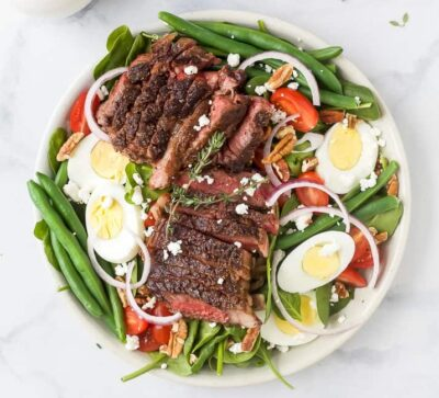 overhead photo of the ultimate ribeye steak salad with hardboiled eggs, tomatoes, onions