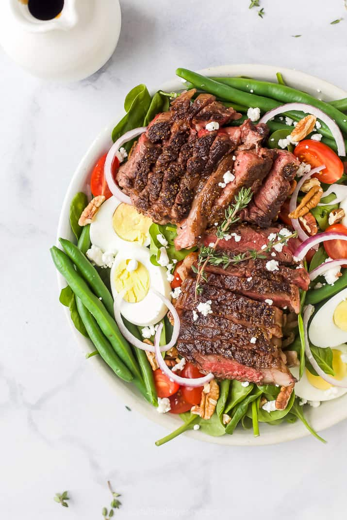 overhead photo of overhead photo of the ultimate ribeye steak salad with hardboiled eggs, tomatoes, onions