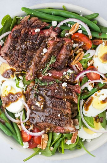 closeup overhead photo of the ultimate ribeye steak salad with hardboiled eggs, tomatoes, onions